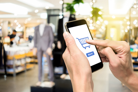 One using smartphone for e-commerce to buy men fashion wear. Plastic models in blank and gray suit standing in front of the shop.
