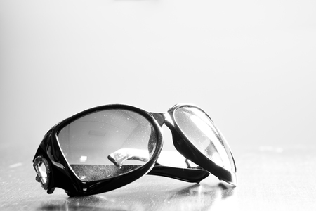 monotone: Old dirty sunglasses on wooden table. Monotone effect. Stock Photo