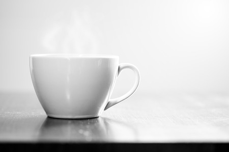 monotone: Coffee in white cup on wooden table and morning light is shining. Monotone effect.