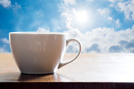 monotone: Hot coffee in white cup on wooden table and morning sunlight is shining. Monotone effect.