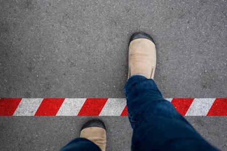 Uno cammina attraverso la linea rossa e bianca verso l'area proibita. Rompere la regola oltre il limite. Archivio Fotografico - 72267899