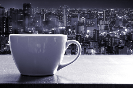 Hot coffee in white cup on wooden counter bar beside the glass window on high tower with Osaka city night view. Monotone effect.