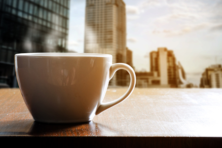 Hot coffee in white cup on wooden table in coffee shop or cafe. Beside the window on high tower in the morning. City view outside the window.