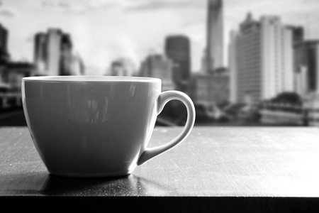 Hot coffee in white cup on wooden table in coffee shop or cafe. Beside the window on high tower in the morning. City view outside the window. monotone effect. Stock Photo