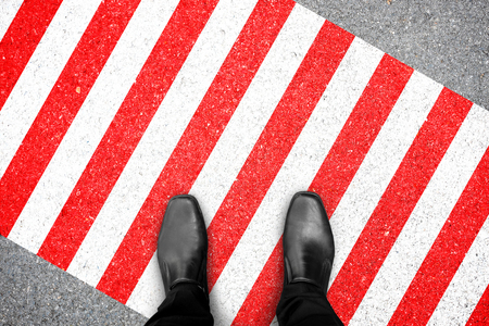 Homme d'affaires en chaussures noires debout sur une zone réglementée en rouge et blanc.