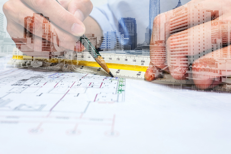 Double exposure engineer are measuring distance in drawing using pencil and ruler and city.
