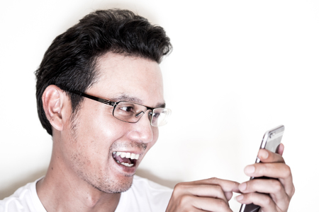 near sighted: Handsome asian man with light beard and curly hair wearing eyeglasses for near sighted using smartphone.  Laughing and happy.