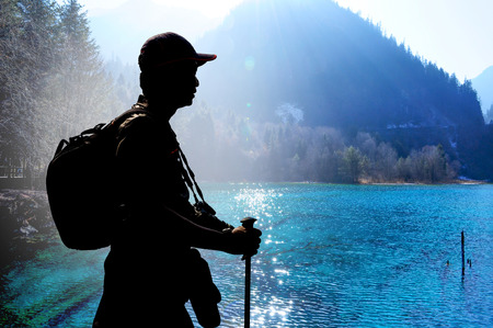 frozen lake: Trekker feeling tired and resting at colorful turquoise lake in spring season - Jiuzhaigou, China Stock Photo