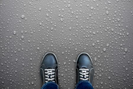 Caution, wet floor. Black shoes standing on wet floor. Slippery and dangerous. Need careful walk.