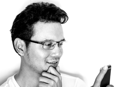 Handsome asian man with light beard and curly hair wearing eyeglasses for near sighted using smartphone.  Smile and happy. Monotone effect.