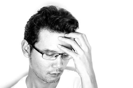 Handsome asian man with light beard and curly hair wearing eyeglasses for near sighted feeling depressed and headache. Monotone effect.
