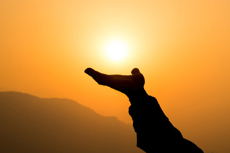 Hand reaching to the golden sun over the mountain in the morning representing conceptual of success and hope. 版權商用圖片 - 82259826
