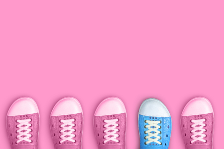 Blue right shoe between pastel pink left shoes on pastel pink background for minimal concept of differennce and outstanding.