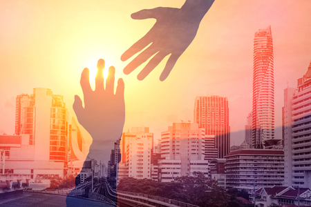 Helping hands concept. Silhouette of hands help and hope and support each other in urban city life. Archivio Fotografico