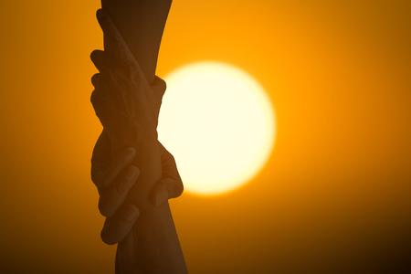 Silhouettieren Sie die Handhände, die zusammen unter der Sonne halten, die Freundschaft, Partnerschaft, Hilfe und Hoffnung, Spende, Unterstützung darstellt. Standard-Bild