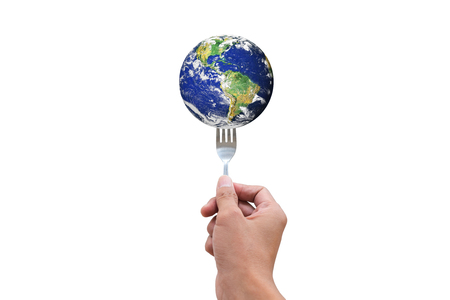 Environment conservation concept. Hand holding fork with the earth ready to eat. Energy consumption concept. Elements of this image furnished by NASA.