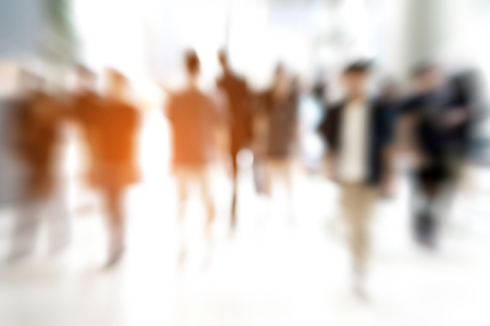 Abstract zoom blur people walking and sunlight shining from behind. Urban life. Stock Photo