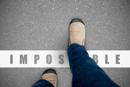 One wearing jeans and brown suede shoes walking over the impossible line representing positive can do and everything possible concept. 免版税图像