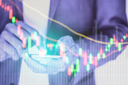 Businessman using smartphone for data analysis and stock trading.