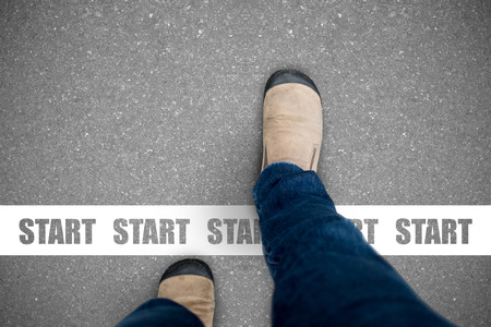 One wearing jeans and brown suede shoes walking across the start line representing business and life start up concept.