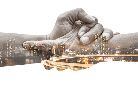 Double exposure help hands holding together and urban city at night representing friendship, partnership, help and hope, donation, assistance. Helping old, poor and hunger.