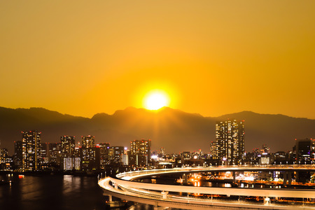 Sunrise and sunset over the mountain behind big city. Stock Photo