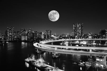 Dramatic black and white full moon over big city and seaport with cargo ship.