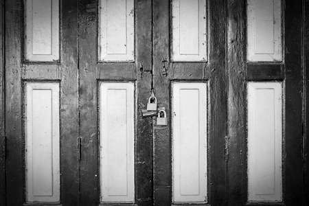 Dramatic black and white old style green and white door in Bangkok, Thailand and key locked.