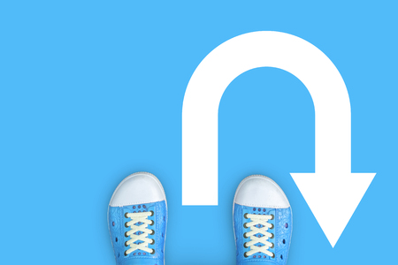 Minimal concept of u-turn, turn around and backward. Blue shoes standing on the floor and u turn sign.
