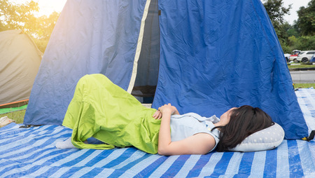 Woman sleeping on plastic field mat outside the tent in the afternoon.