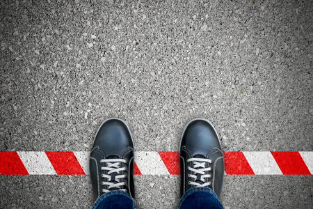 Black shoes standing on the red-white line. Breaking the rule. It's prohibited and not allowed. It's limited. It's the end. Banque d'images