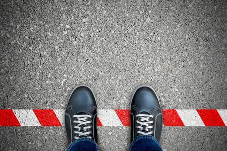 Schwarze Schuhe stehen auf der rot-weißen Linie. Die Regel brechen. Es ist verboten und nicht erlaubt. Es ist begrenzt. Es ist das Ende.