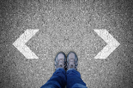 Outdoor shoes standing at the crossroad making decision which way to go.