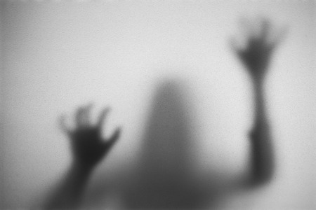 Shadow of woman on the frosted glass representing dangerous, fear, help, haunting, horror and scary. Stock Photo