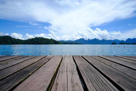 Piso de tarima de madera con hermoso lago. Fondo de naturaleza tropical.