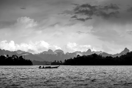 Dramatic black and white boat in the lake, Suratthani, Thailand.