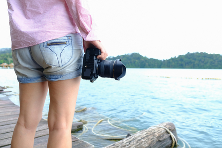Female photographer in short jeans holding professional dslr camera standing on wooden platform watching nature in the lake.