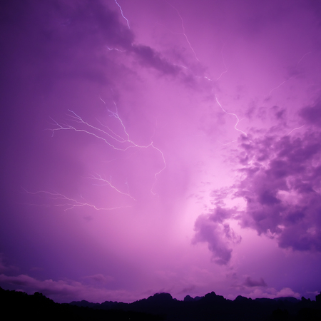 Lightning bolt striking at night with purple cloudy sky. Imagens