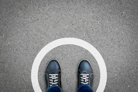 Chaussures noires debout dans un cercle blanc sur le sol en béton asphalté. Concept de limite, frontière, cadre, etc.