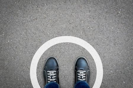 Zapatos negros de pie en círculo blanco sobre el piso de concreto asfáltico. Concepto de límite, contorno, marco, etc.