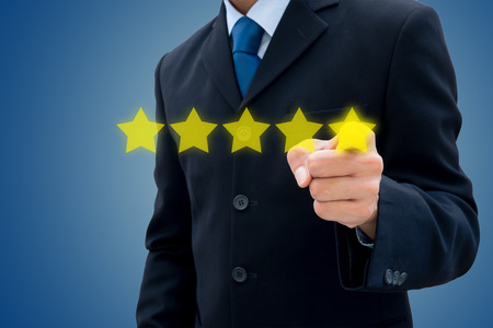 Review, rating, ranking concept. Hand pushing on five stars for best rating.