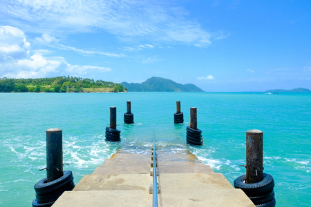Tourist pier in Phuket island sea, Thailand with blue sea and clear summer sky.