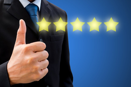 Isolated businessman in dark grey suit raising his thumb up with five stars represent business success.