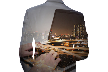 Business and technology concept. Double exposure businessman with computer laptop and city at night.