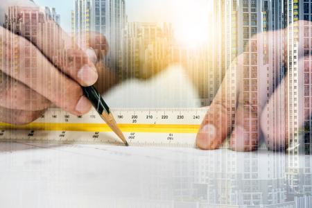 El ingeniero de doble exposición mide la distancia en el dibujo con lápiz y regla y ciudad. Concepto de ingeniería y arquitecto. Foto de archivo