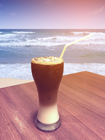 Iced coffee and cream in tall glass with straw on wooden table at the beach.