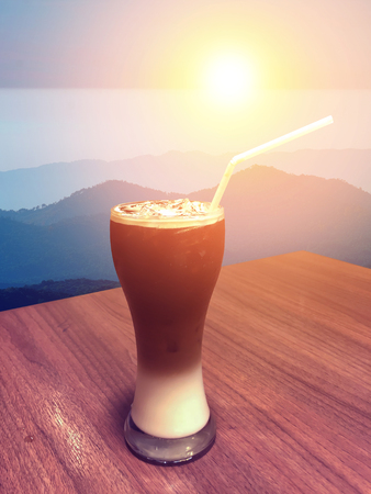 Iced coffee and cream in tall glass with straw on wooden table on the mountain.