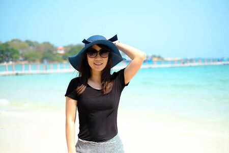 Portrait of Asian woman wearing blue hat smiling on the beach of Samed Island, Thailand.