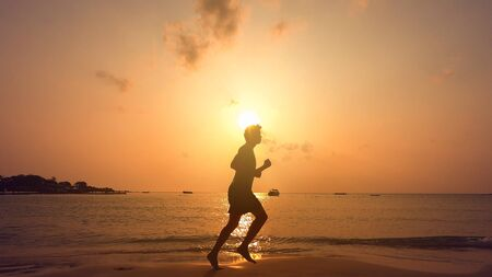 Man barefoot running on the beach at sunset