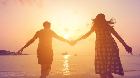Happy couple holding hands running to the sea at sunset Imagens